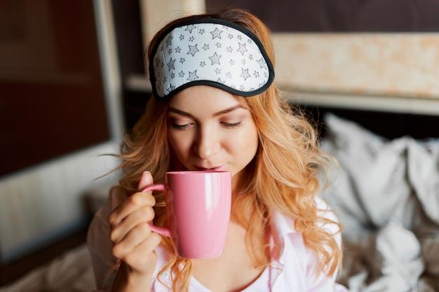 Pełen wdzięku kobieta z szczerym uśmiechem pozowanie w masce na oczy w jej sypialni i picie gorącej herbaty.