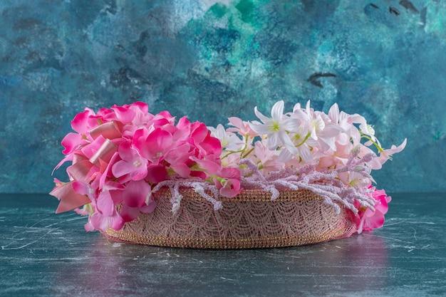 Pełen wdzięku kwiat w misce, na niebieskim tle.