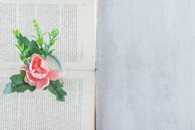 Pełen wdzięku kwiaty w słoiku na książce, na białym stole.