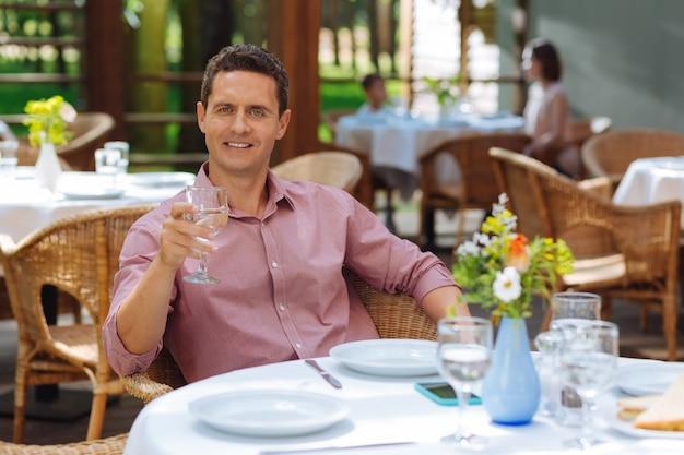 Pełen wdzięku mężczyzna. pełen wdzięku przystojny dojrzały mężczyzna siedzi przy stole na letnim tarasie jedząc obiad
