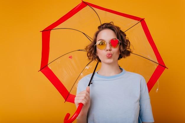 Pełen wdzięku młoda kobieta w niebieskiej koszuli z całowania wyrazem twarzy. studio strzał ładnej modelki z kręconymi włosami, wygłupiać się podczas sesji zdjęciowej z parasolem.