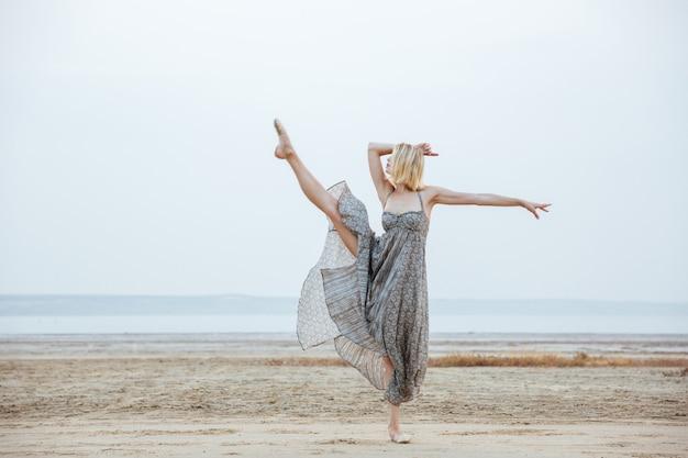 Pełen wdzięku młoda tancerka w pięknej sukni tańczy na plaży