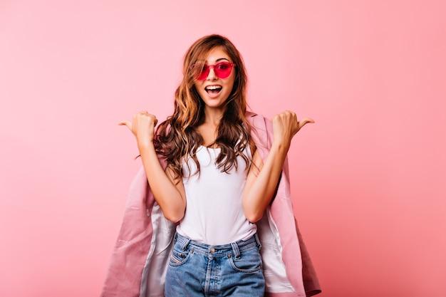Pełen wdzięku rudy młoda kobieta w modnych okularach chłodzi podczas sesji portretowej. portret entuzjastycznej słodkie dziewczyny wyrażające dobre emocje.