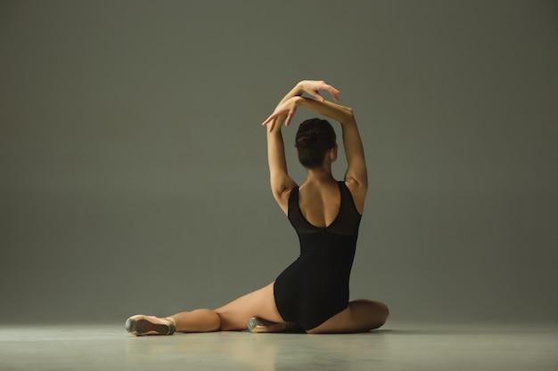 Pełen wdzięku tancerz baletowy lub baleriny klasyczny taniec na białym tle na szarym tle studio. okazywanie elastyczności i wdzięku. koncepcja tańca, artysty, współczesności, ruchu, akcji i ruchu.