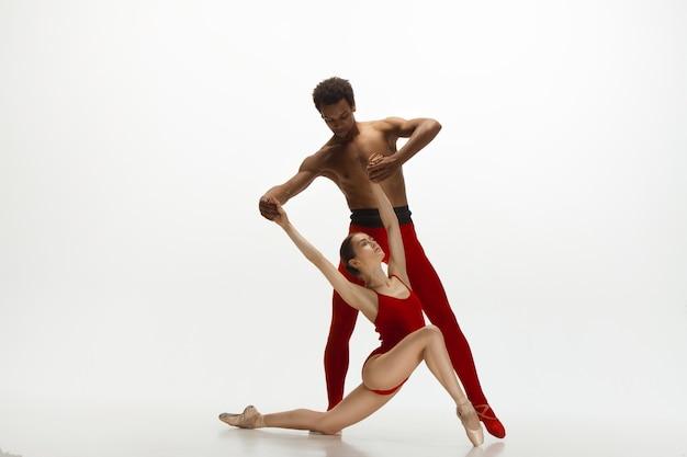Pełen wdzięku tancerzy baletu klasycznego, taniec na białym tle na tle białego studia. para w jaskrawoczerwonych ubraniach przypominających połączenie wina i mleka. koncepcja łaski, artysty, ruchu, akcji i ruchu.