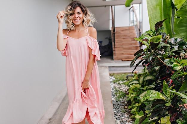 Pełen wdzięku uśmiechnięta dziewczyna w długiej sukni z kręconymi włosami. plenerowe zdjęcie wyrafinowanej opalonej kobiety w różowym stroju.
