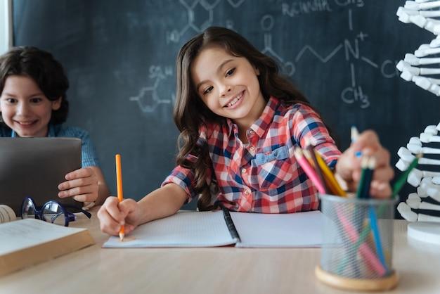 Pełen żywych emocji. zdolna, utalentowana śliczna dziewczyna siedzi w szkole i bawi się zajęciami plastycznymi, pracując nad projektem i używając kolorowych ołówków
