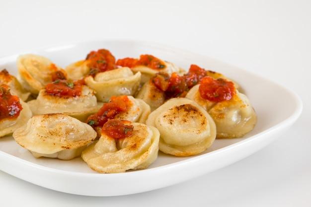 Pelmeni rosyjskie jedzenie, smażone pierogi mięsne na białym talerzu, z sosem pomidorowym