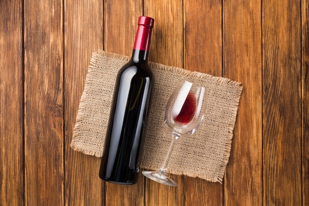 Pełna butelka czerwonego wina i pusta szklanka