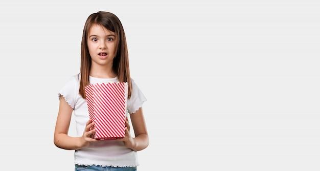 Pełna ciało mała dziewczynka szczęśliwa i zafascynowana, trzymając wiadro popcornu w paski
