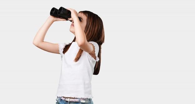 Pełna ciało mała dziewczynka zaskoczona i zdziwiona, patrząc z lornetką w oddali coś ciekawego, koncepcja przyszłej możliwości