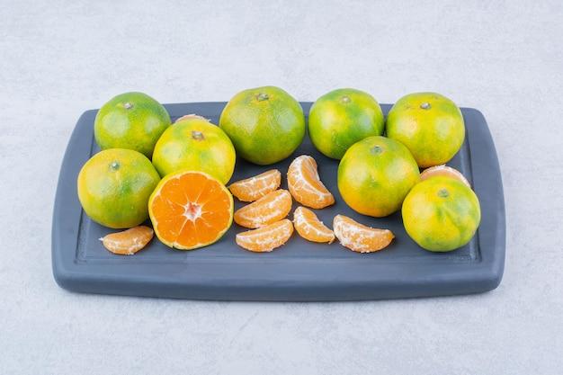 Pełna ciemna deska do krojenia kwaśnych mandarynek na białym tle. zdjęcie wysokiej jakości