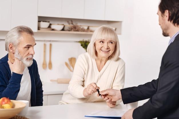 Pełna determinacji. doświadczony biegły i wykwalifikowany doradca ds. ubezpieczeń społecznych prowadzący rozmowy ze starszymi klientami i pracujący przy przygotowywaniu dokumentów do podpisu
