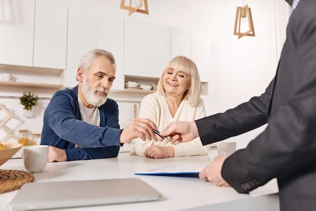 Pełna determinacji. zdecydowana wesoła para w podeszłym wieku siedzi w domu i rozmawia z doradcą ds. ubezpieczeń społecznych przy podpisywaniu umowy