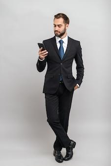 Pełna długość atrakcyjnego młodego biznesmena w garniturze stojącego na białym tle nad szarą ścianą, trzymającego telefon komórkowy