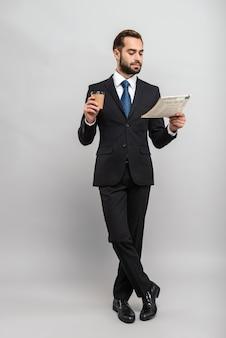 Pełna długość atrakcyjnego uśmiechniętego młodego biznesmena w garniturze izolowanym na szarej ścianie, czytającego gazetę podczas picia kawy na wynos