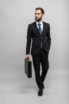 Pełna długość atrakcyjnego uśmiechniętego młodego biznesmena w garniturze izolowanym na szarej ścianie, niosącego teczkę, spacerującego