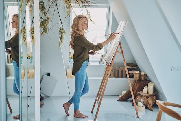 Pełna długość atrakcyjnej młodej kobiety malującej w studiu artystycznym