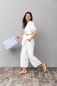 Pełna długość atrakcyjnej młodej kobiety w letnim stroju, stojącej na białym tle nad szarą ścianą, niosącej torby na zakupy