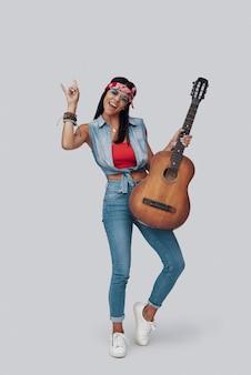 Pełna długość atrakcyjnej stylowej młodej kobiety niosącej gitarę akustyczną i uśmiechającej się stojąc na szarym tle