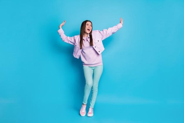 Pełna długość beztroskiej nastoletniej dziewczyny bawiącej się w tańcu na białym tle na niebieskim tle