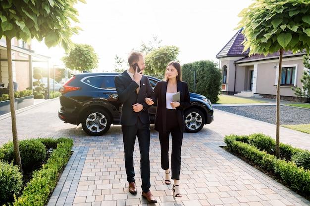 Pełna długość biznesmena i bizneswomanu odprowadzenie na zewnątrz budynku biurowego na biznesowym spotkaniu, outdoors. spotkanie ludzi biznesu