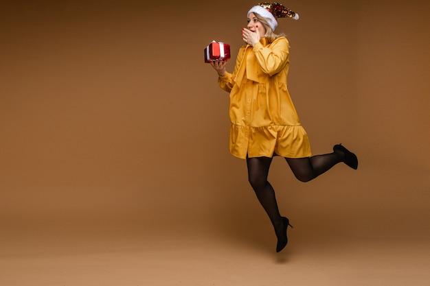 Pełna długość blond kobiety rasy kaukaskiej w żółtej sukience, rajstopach, szpilkach i błyszczącej czapce mikołaja niosącej zapakowany prezent świąteczny w powietrzu zakrywający usta z podekscytowania