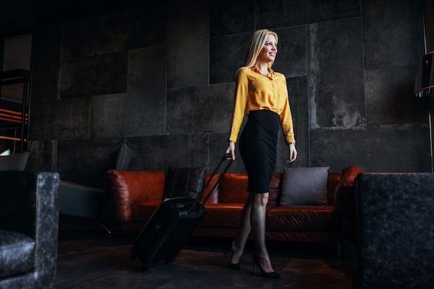 Pełna długość blondynki w średnim wieku w oficjalnym stroju ciągnąca walizkę i opuszczająca hotel.