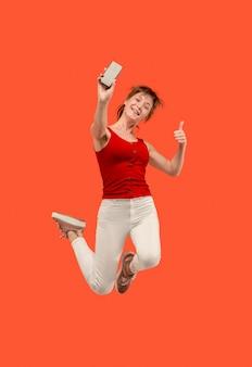 Pełna długość całkiem młoda kobieta biorąc telefon podczas skoków na czerwonym tle studio.