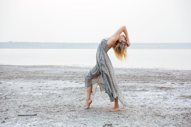 Pełna długość całkiem młoda kobieta w sukience tańczy boso na plaży