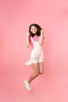 Pełna długość całkiem podekscytowanej młodej nastolatki skaczącej odosobnionej, radującej się, kciuki w górę