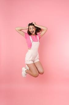 Pełna długość całkiem podekscytowanej młodej nastolatki skaczącej odosobnionej, radującej się