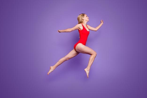 Pełna długość całkiem wesołej pani skaczącej na fioletowo