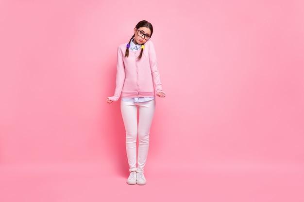 Pełna długość ciała jej rozmiar jest ładny atrakcyjny całkiem ładny nieśmiały sprytny mądry brązowowłosa dziewczyna geek stojący wzruszając ramionami na białym tle nad różowym pastelowym kolorem tła