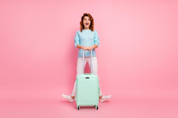 Pełna długość ciała, jej rozmiar, widok jej jest ładna, atrakcyjna śliczna, bardzo zadowolona, wesoła, wesoła, falowana dziewczyna niosąca bagaż zabawy na białym tle nad różowym pastelowym kolorem tła