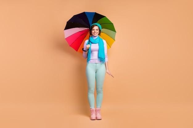 Pełna długość ciała jej rozmiar widok jej jest ładna, atrakcyjna, urocza, bardzo modna, wesoła, wesoła dziewczyna ubrana w miętową, lawendową odzież, trzymającą parasol na białym tle nad beżowym pastelowym kolorem tła