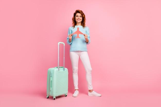 Pełna długość ciała, jej rozmiar, widok jej jest miła, atrakcyjna, całkiem wesoła, falista dziewczyna trzymająca w rękach papierowy samolot odlatujący z wakacji na białym tle nad różowym pastelowym kolorem tła