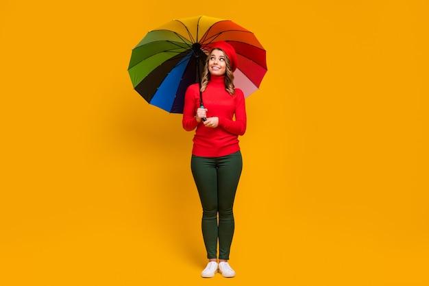 Pełna długość ciała, jej rozmiar, widok na nią ładna, atrakcyjna, urocza, modna, wesoła, falowana dziewczyna trzymająca w ręku parasol na jasnym, żywym połysku, żywy, żółty kolor tła