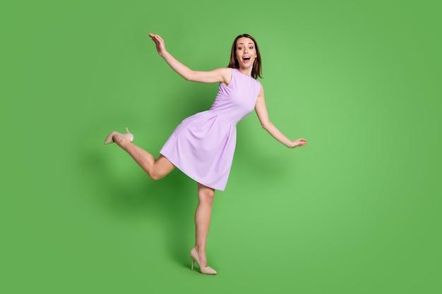 Pełna długość ciała rozmiar jej widok ona ładna atrakcyjna śliczna dość elegancka wesoła wesoła dziewczyna tańczy zabawę spędza wolny czas wolny czas na białym tle na zielonym tle