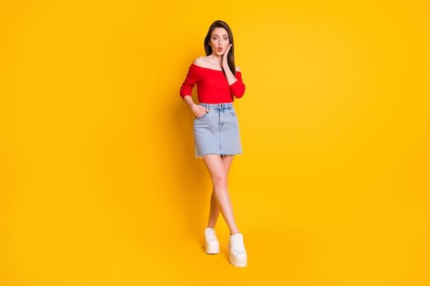 Pełna długość ciała rozmiar jej widok ona ładna atrakcyjna śliczna śliczna szczupła zdumiona dziewczęca wesoła dziewczyna dąsa usta niesamowite wiadomości odizolowane na jasnym żywym połysku żywy żółty kolor tła