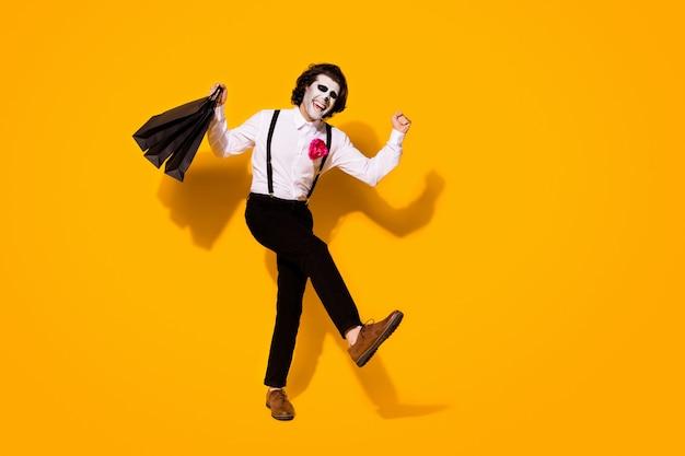 Pełna długość ciała rozmiar widok jego ładny przystojny straszny wesoły wesoły ekstatyczny podekscytowany zadowolony facet dżentelmen niosący zakupy zabawy na białym tle jasny żywy połysk żywy żółty kolor tła