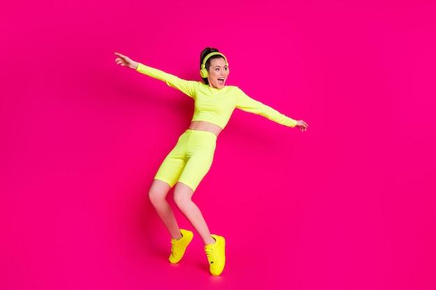 Pełna długość ciała rozmiar widok jej ona ładne atrakcyjne dopasowanie szczupły sportowy funky wesoła dziewczyna słuchanie muzyki taniec zabawy oszukiwanie na białym tle jasny żywy połysk żywy różowy fuksja kolor tła