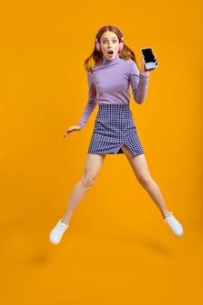 Pełna długość ciała rozmiar widok ładnej, wesołej, wesołej kobiety w słuchawkach, skaczących, bawiących się przy użyciu szybkiego połączenia smartfona, słuchać muzyki na białym tle na żółtym tle