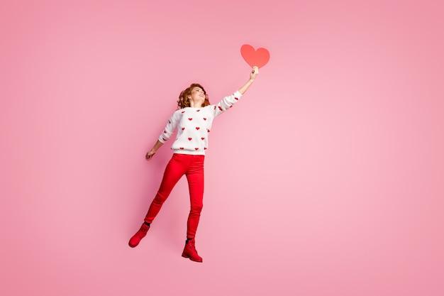 Pełna długość ciała widok beztroskiej wesołej lśniącej dziewczyny skaczącej trzymającej w ręku kartkę z gratulacjami wróżkę