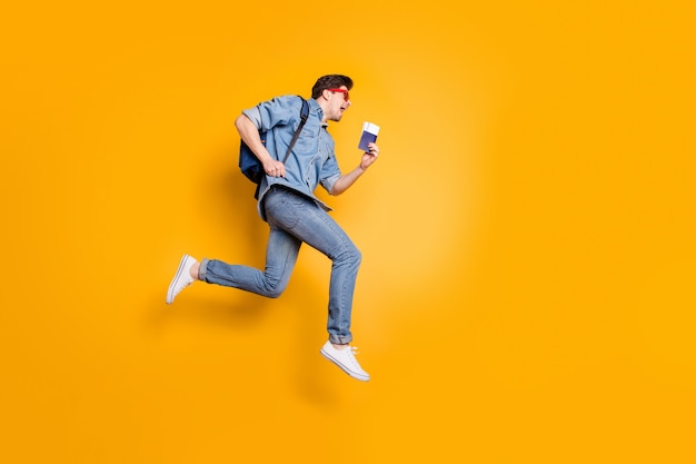 Pełna długość ciała widok ładnego atrakcyjnego, wesołego, wesołego faceta skaczącego sezon biegowy wycieczka reszta trzymająca w ręku bilety odizolowane na jasnym, żywym połysku, wibrującym żółtym kolorze ściany