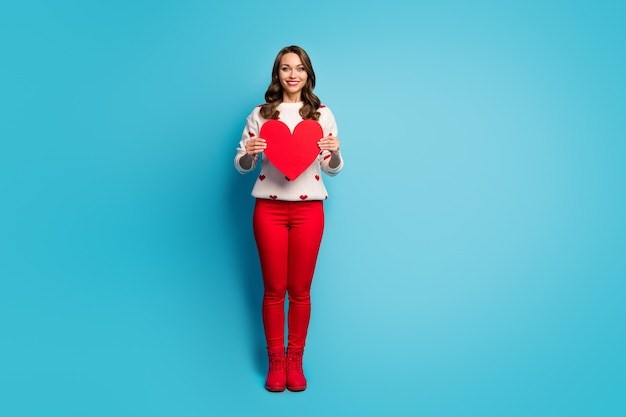 Pełna długość ciała widok ładnej, atrakcyjnej, kochanej, radosnej, marzycielskiej dziewczyny w świątecznych ubraniach trzymającej w ręku wielkie serce