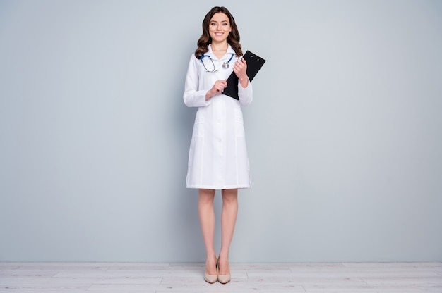 Pełna długość ciała widok ładnej, atrakcyjnej, wesołej, radosnej treści wykwalifikowana pielęgniarka z falowanymi włosami trzymająca w rękach dokument medicare 247 nagły wypadek odizolowany na szarym tle