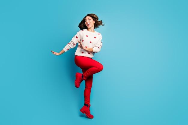 Pełna długość ciała widok urocza, wesoła, wesoła, radosna dziewczyna skacząca i tańcząca dyskoteka