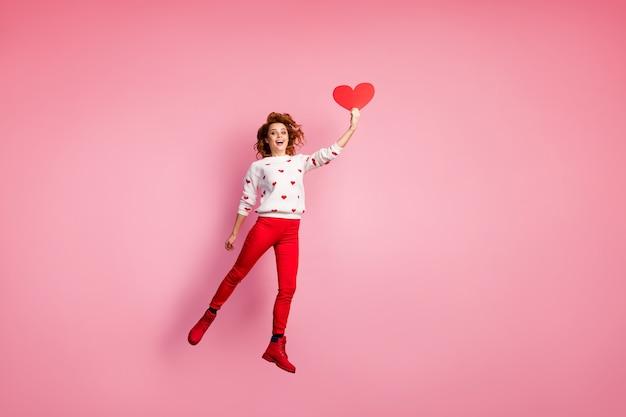 Pełna długość ciała widok wesołej lśniącej dziewczyny skaczącej trzymając w ręku gratulacje z sercem