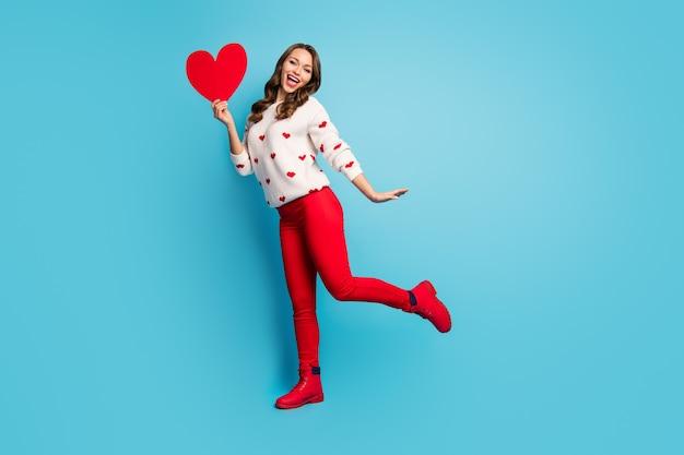 Pełna długość ciała zobacz uroczą wesołą figlarną dziewczynę trzymającą w ręku wielkie serce zabawę tańczącą